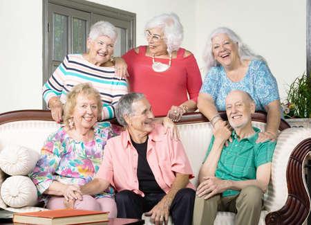 Six senior friends laughing around an antique couch Foto de archivo - 142915651