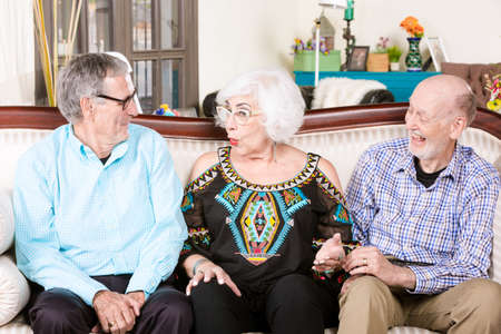 Two senior men with woman on a living room couch