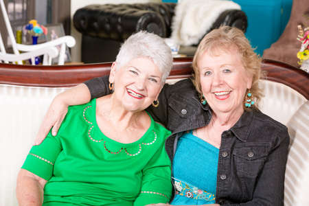 Two senior women sitting together on a couch smiling
