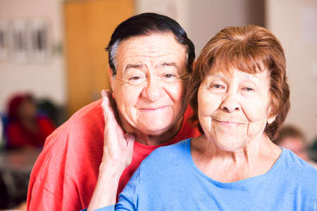 Smiling Hispanic couple laughing  in a busy senior center