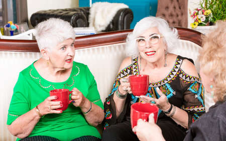 Three senior women having a coffee or tea and talking Foto de archivo - 142915659