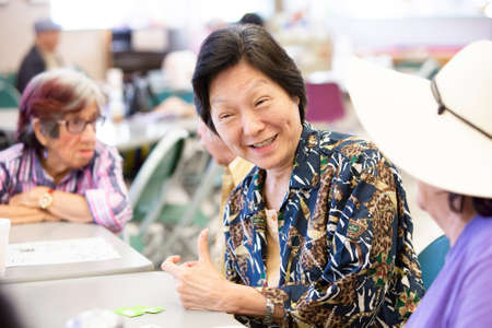 Chinese woman smiling and talking in a senior center