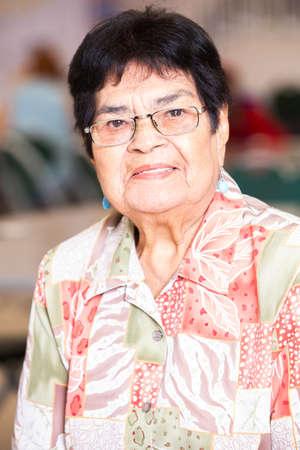 Smiling Latina woman in a busy senior center Foto de archivo - 142915769