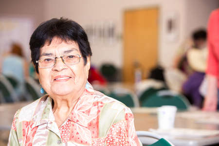 Hispanic woman smiling in a busy senior center Foto de archivo