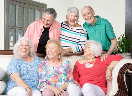 Six laughing senior friends around an antique couch Foto de archivo