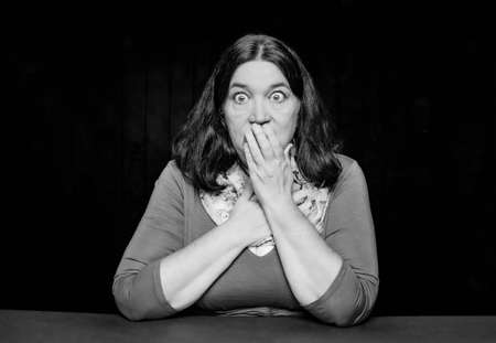 Black and white shocked woman with a hand over her mouth