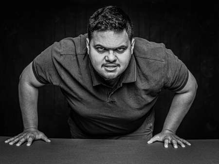 Black and white Latino man leaning in an aggressive manner