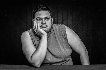 Black and white bored or distracted Latino man with arms bared