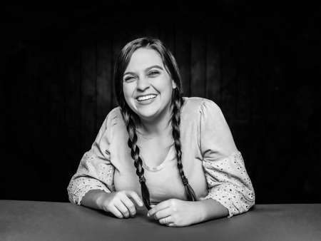 Black and white portrait of happy laughing  young woman leaning on table with hair in braids Foto de archivo