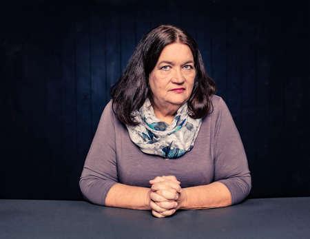Portrait of serious mature woman wearing a scarf Foto de archivo - 143000545