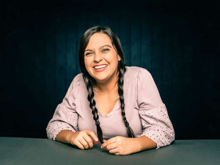 Portrait of happy laughing  young woman leaning on table with hair in braids Foto de archivo