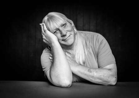 Black and white seated portrait of a blonde trans woman resting head on her hand Foto de archivo - 144205592