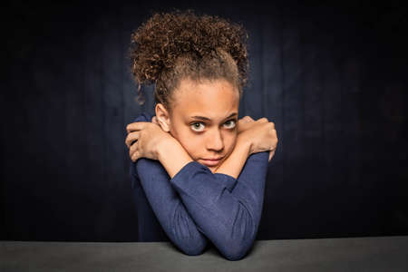 Pretty young girl resting her head on crossed arms