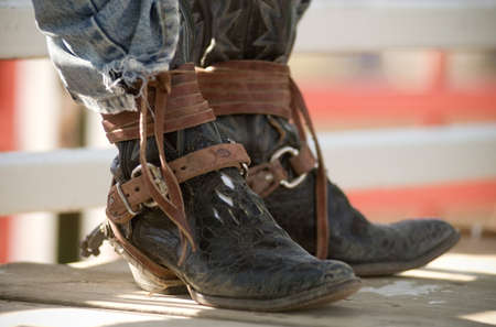 Cowboy Boots worn by a Rodeo Rider between rides wearing a pair of dusty worn leather cowboy boots with suede leather straps wrapped around, buckles and spurs