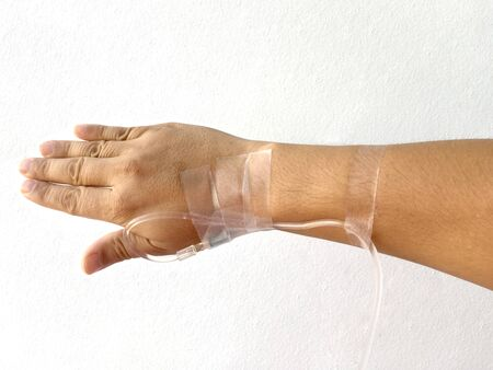 Focus on the hand of a patient in hospital ward on white background. Reklamní fotografie