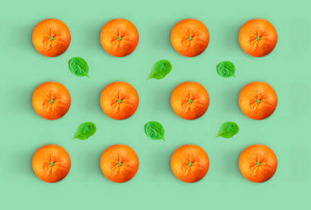 Oranges and spinach leaves pattern.Creative Minimal orange concept. fresh oranges in color background Foto de archivo - 122306031