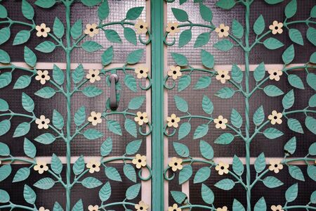 Turquoise vintage floral glass door with white flowers.