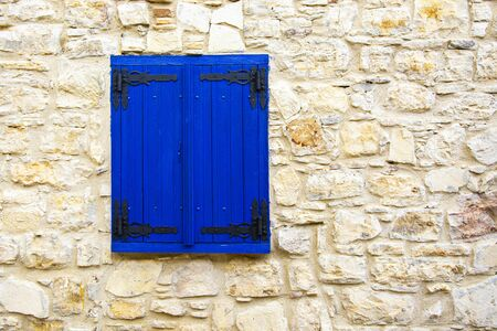 An old rustic blue wooden window in a village in Cyprus