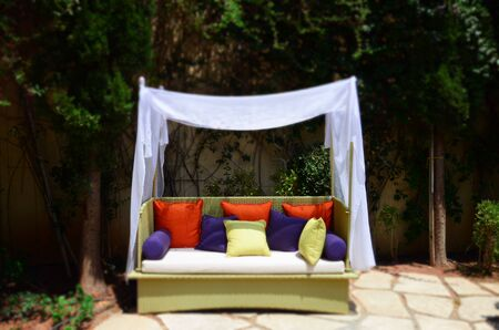 Classy Garden Furniture with Colourful Pillows and White Sheets 版權商用圖片