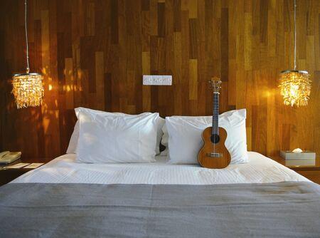 Luxury Hotel Bed with a Ukulele on it. 版權商用圖片