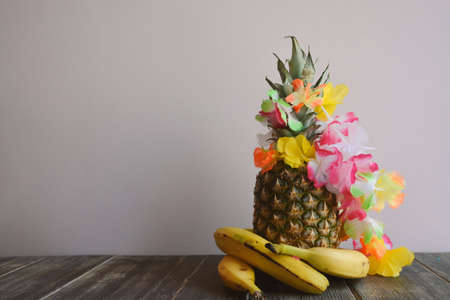 Decorative Pineapple with Bananas and Flowers on a Wooden Table