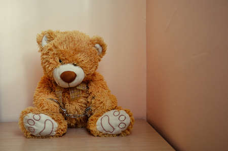 Sad Brown Handcuffed Teddybear Concept Photo 版權商用圖片
