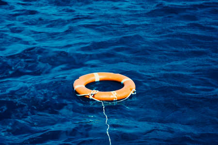 An Orange Lifebuoy Floating in the Middle of the Ocean