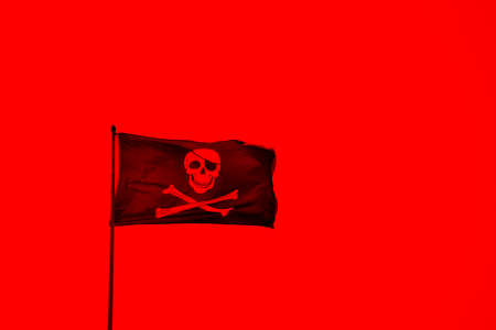 A red coloured pirate flag with with skull and bones