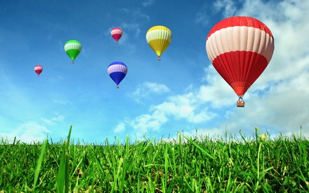 Globos de aire caliente flotando sobre el campo verde Foto de archivo
