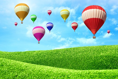 Hot air balloons floating over green field  photo
