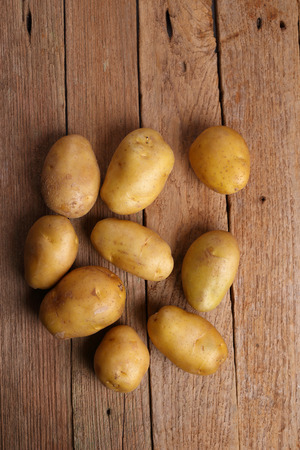 jhy: Potatoes on wooden background Stock Photo