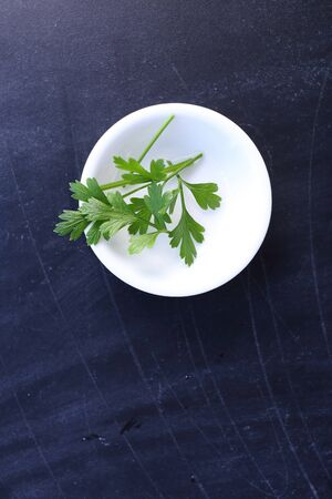 one object: Top view parsley in bowl on black background Stock Photo