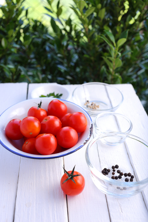 kitchen table top: Tomatoes with ingredients in bowl on white woooden