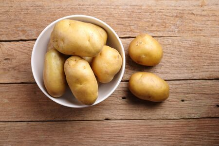 jhy: Top view Potatoes in bowl with wooden background Stock Photo