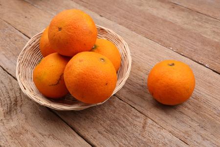 wooden basket: Orange fruit in basket on wooden background