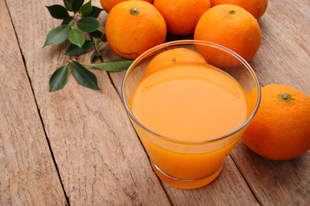 natural juices: Ornage fruit on wooden background Stock Photo