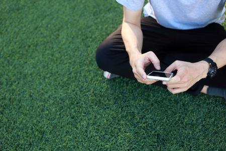 cellular: man sitting use smartphone on artificial turf