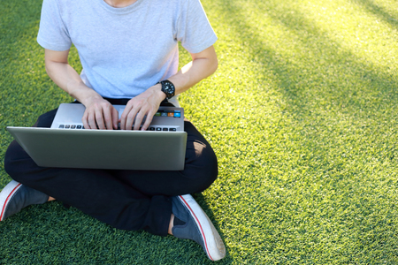 green technology: man sitting use laptop on artificial turf