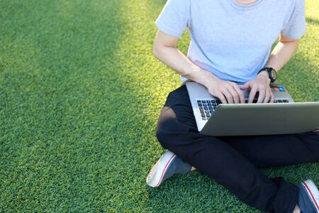 use computer: man sitting use laptop on artificial turf