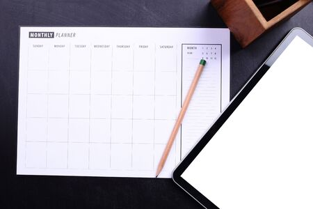 electronic organiser: Planner schedule with pencil and blank screen tablet on black wooden