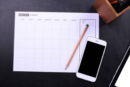 electronic organiser: blank screen smartphone and planner schedule on black wooden background Stock Photo
