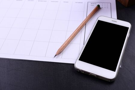 blank screen smartphone and planner schedule on black wooden background Stock Photo
