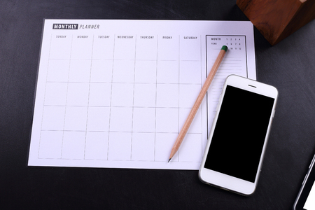 planner: blank screen smartphone and planner schedule on black wooden background Stock Photo
