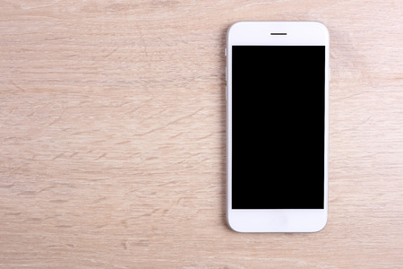 Blank screen smartphone on wooden background