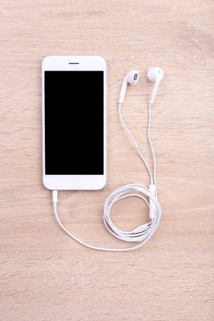 phone button: Blank screen smartphone with earphone on wooden background