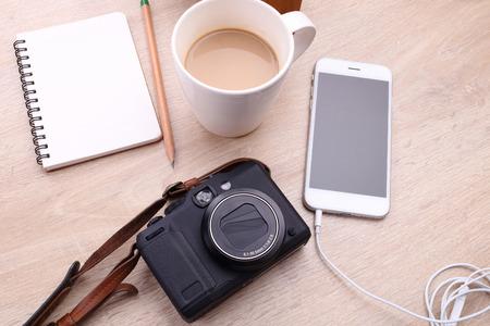 cámara digital, teléfono inteligente con el papel de nota y el café sobre fondo de madera