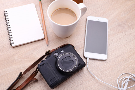 compact camera: Digital camera, Smartphone with note paper and coffee on wooden background Stock Photo