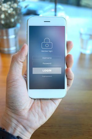 loging: Hand holding smartphone with mebber loging screen on coffee shop background Stock Photo