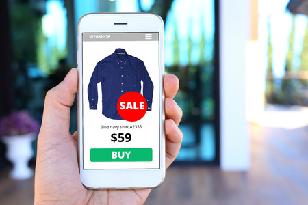 mobile app: Hand holding smartphone with ecommerce screen website