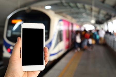 subway station: Hand holding smartphone with subway station background